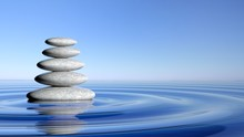 Zen Stones Stack From Large To Small  In Water With Circular Waves And Blue Sky.