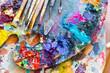 Leinwandbild Motiv Closeup of art palette with colorful mixed paints and paintbrushed