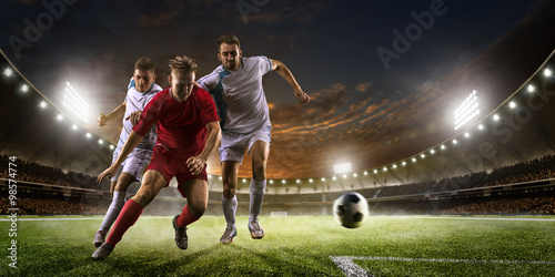 Soccer players in action on sunset stadium background panorama - 98574774