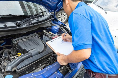 Zdjęcie XXL Mechanika mężczyzna mienia schowek i sprawdza samochód