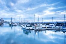 Skyline And Sailing Boats Along Dock On Sea