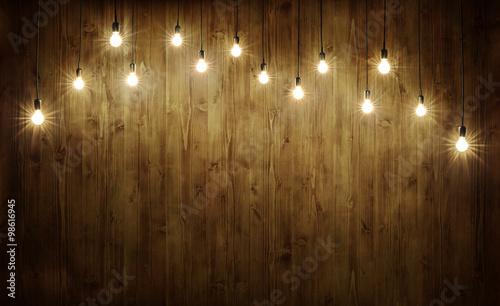 Fotografiet  Light bulbs on wood