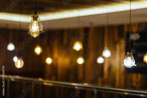 Vintage incandescent bulb on brick wall background Poster