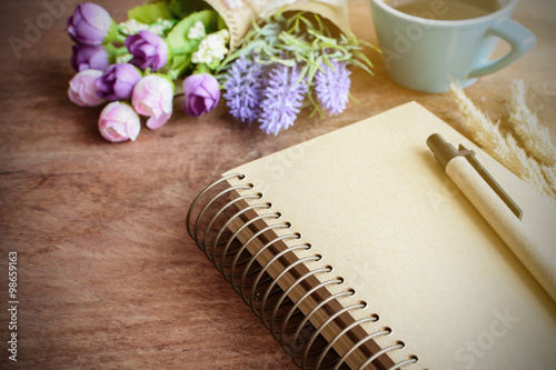 Fotografie, Tablou  Cup of coffee with flower and blank notebook on wooden table