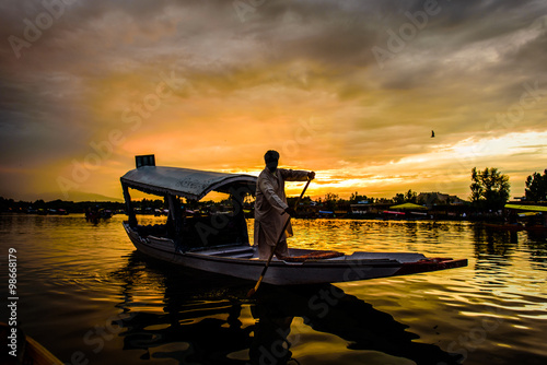 Photo  The silhouette of a boat glides along the surface of Dal Lake du