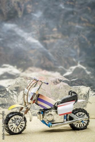 Fotografia, Obraz  Spielzeug Motorrad aus Blech auf Sandpiste