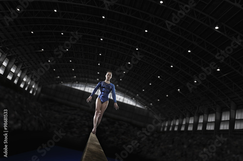 Tuinposter Gymnastiek A gymnast with her arms by her side on a balance beam