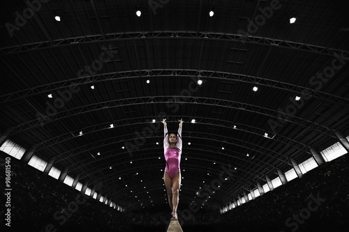 Foto op Aluminium Gymnastiek A gymnast with her arms raised and back arched