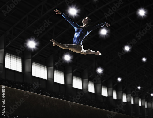 Tuinposter Gymnastiek A gymnast leaping in the air doing the splits