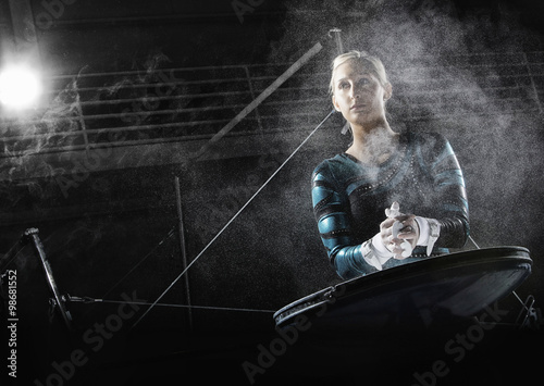 Poster de jardin Gymnastique a female gymnast preparing for a routine, powdering her hands