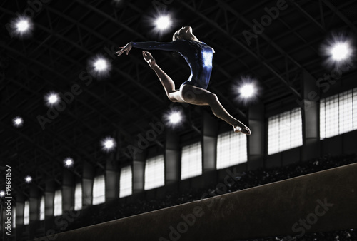 Tuinposter Gymnastiek a female gymnast leaping in the air, back arched