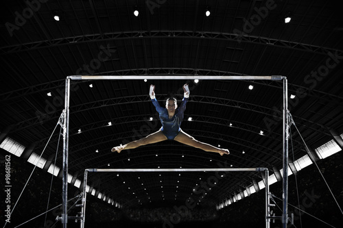 Spoed Fotobehang Gymnastiek A gymnast on the parallel bars performing a routine