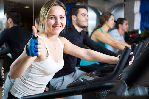 Poster Fitness Active adults riding stationary bicycles