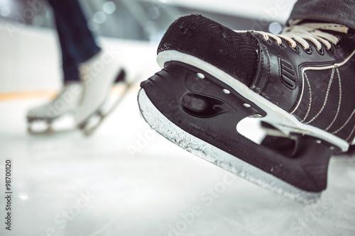 Photo  Man's hockey skates and women's figure skates on ice background