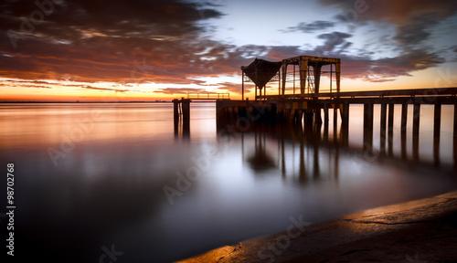 Valokuvatapetti Ancient industrial pier over a sunrise