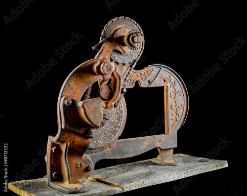 Fotografie, Obraz  Antique very rusty meat slicer on rustic barn wood against a black background
