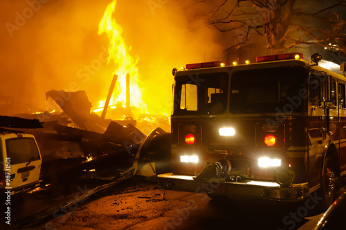 Fotografie, Obraz  Major building fire with fire engine, smoke and heavy flame.