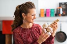 Closeup Of Woman Holding Up Bunch Of Garlic
