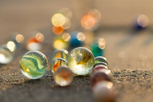 Marbles On The Sidewalk In Golden Sunlight.