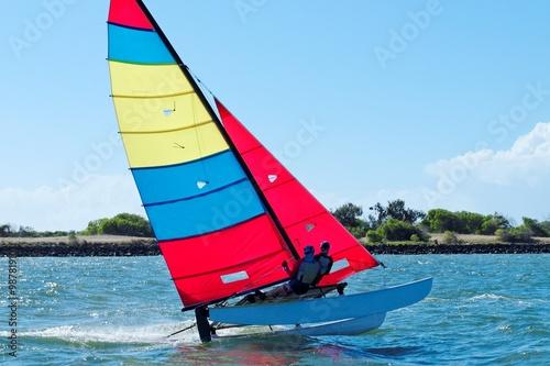 Poster Zeilen Racing Cat sailing with Blue Sky