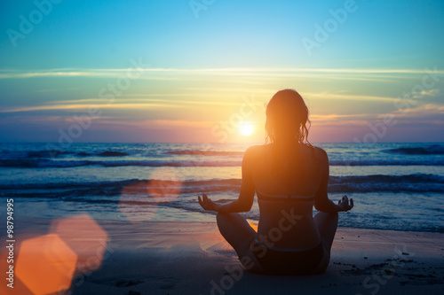 Fotografia  Silhouette young woman practicing yoga on the beach at sunset.