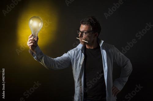 Fotografie, Obraz  Uomo tiene una lampadina accesa in mano