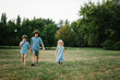 Three kids walking on grass in park on summer afternoon in park and playing to each other