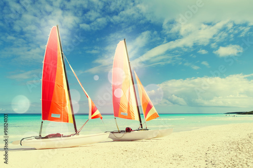 Two catamarans with its colorful sails wide open on Cuban white Canvas Print
