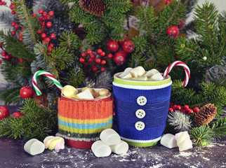 Christmas knitted cups with sweets and conifer branches