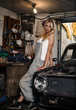 young blonde girl with long hair is an auto mechanic in the garage with a lot of tools on the shelves holding wrenches