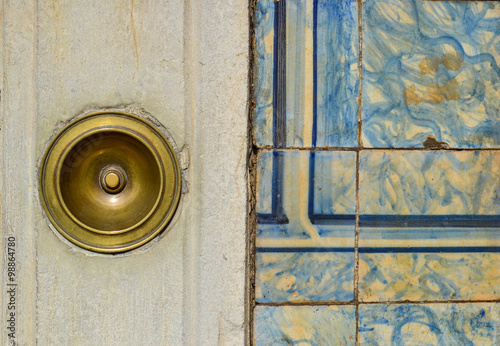 фотографія  Antique brass doorbell on a building facade with ancient tiles