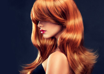 Fototapeta Do fryzjera Beautiful model girl with long red curly hair . Hairstyle and cosmetics