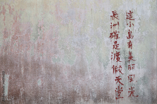 Weathered and old concrete wall with red paint peeled off and Chinese text written with red paint.