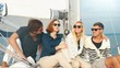 Group of people in sunglasses are relaxing on a yacht in the sea. Shot on RED Cinema Camera.