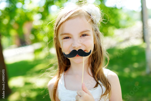 Photo  Adorable little girl playing with paper moustache on a stick