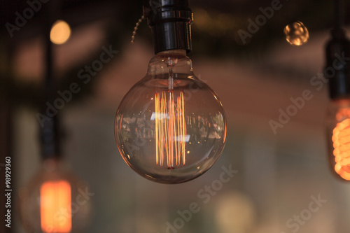 Ornamental light bulb lit up and hanging from the ceiling in a kitchen Canvas Print