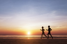 Silhouette Of Two Runners Running On The Beach At Sunset