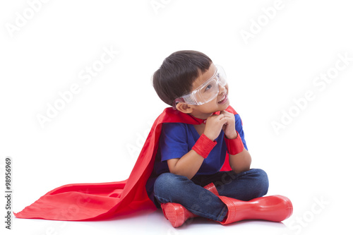 Photo  boy pretending to be a superhero with looking up on white background