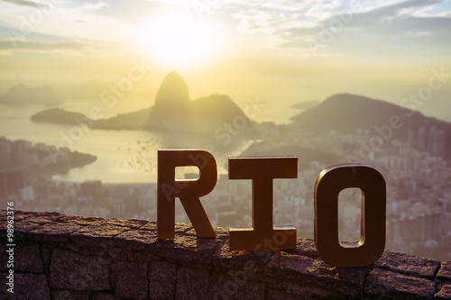 Golden RIO sign standing morning sunrise overlook view of Rio de Janeiro city skyline and Sugarloaf Mountain