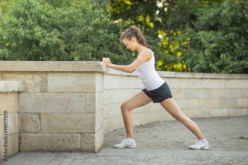 Valokuva  Junge Frau macht Dehnübungen für Beine