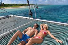 Couple Suntanning On A Catamar...