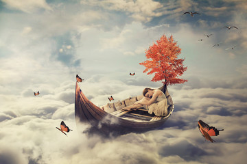 Fototapeta Niebo Young lonely beautiful woman drifting on a boat above clouds. Dreamy screensaver