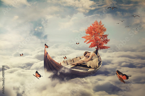 Fototapeta Young lonely beautiful woman drifting on a boat above clouds. Dreamy screensaver obraz