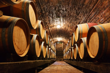 Fototapeta Do winiarni Oak barrels in a underground wine cellar