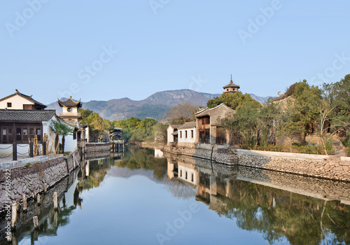 Poster Channel Ancient white Chinese houses reflected in a tranquil canal, Hengdian, China