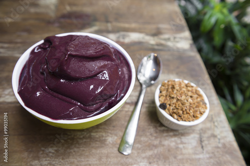 Bowl of fresh Brazilian acai garnished with granola on a rustic wood table in Rio de Janeiro, Brazil
