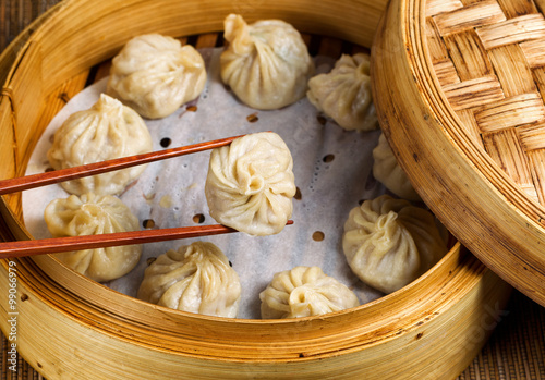 Fotografering Freshly steamed Chinese dumplings out of bamboo steamer