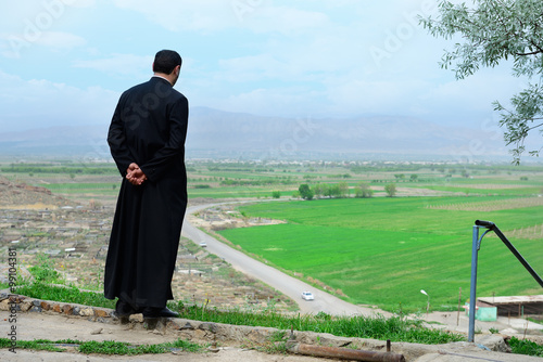Stampa su Tela Armenian priest overlooking scenic fields and mountains