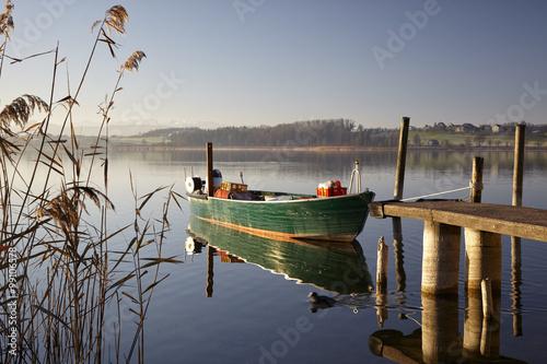 Fotobehang Pier Stimmungsbild vom Pfäffikersee mit vertäutem Fischerboot, Bootssteg, Schilfrohr, und entferntem Seeufer