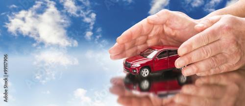 Hände legen sich schützend um ein Auto